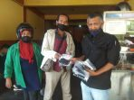 Ketua PWI Tpi-Bintan Zakmi saat menyerahkan masker kain ke salah satu pemilik media di Tanjungpinang
