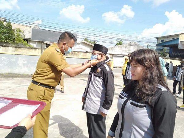 Lurah Kp Bulang Roni Syahputra SH mengenakan masker ke petugas yang akan melaksanakan pembagian masker gratis ke warga