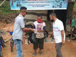 2 anggota Tim WAE saat menyerahkan bantuan sembako ke warga