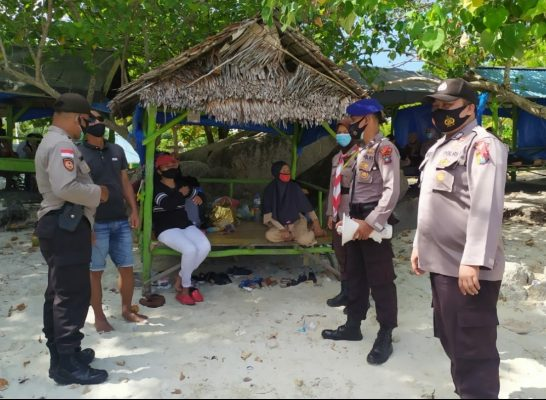 Personil Ops Lilin Seligi 2020 saat mengimbau warga untuk tidak berenang di Pantai Trikora IV