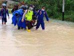 Kapolsek Gunung Kijang AKP Monang P Silalahi bersama rekannya saat mengevakuasi pengguna jalan yang terjebak banjir