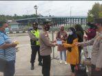 AKP Monang saat membagikan masker ke warga di salah satu pelabuhan di Tanjungpinang