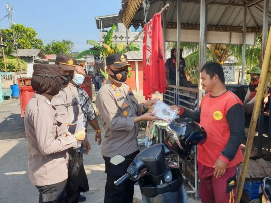 Waka Polsek KKP Monang P Silalahi SH saat membagikan masker di wilayah kerjanya