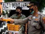 """Kapolres Tanjungpinang AKBP Fernando saat ikut membagikan makanan """"Razia Perut Lapar"""" ke warga"""